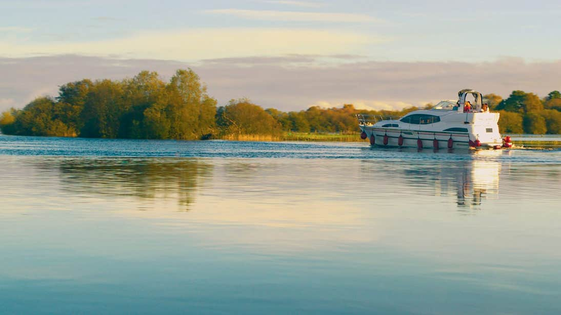 A boat cruising the River Shannon with views of trees nearby
