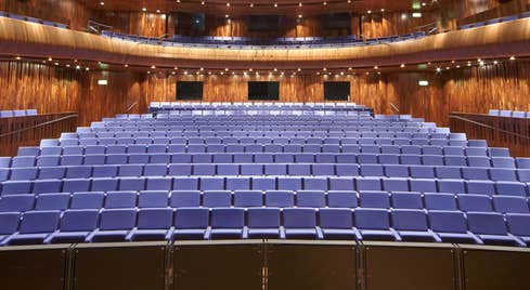 A view from a stage onto an empty seating area surrounded by a balcony
