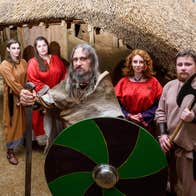 A group of Viking reenactors stand in front of a building carrying a sword, shield and axe.