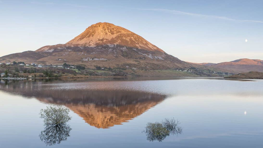 Mount Errigal reflecting onto a lake with the moon in the sky