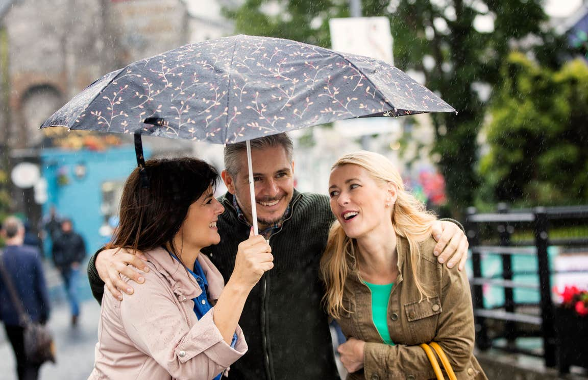 Three people standing under an umbrella in Ennis in County Clare
