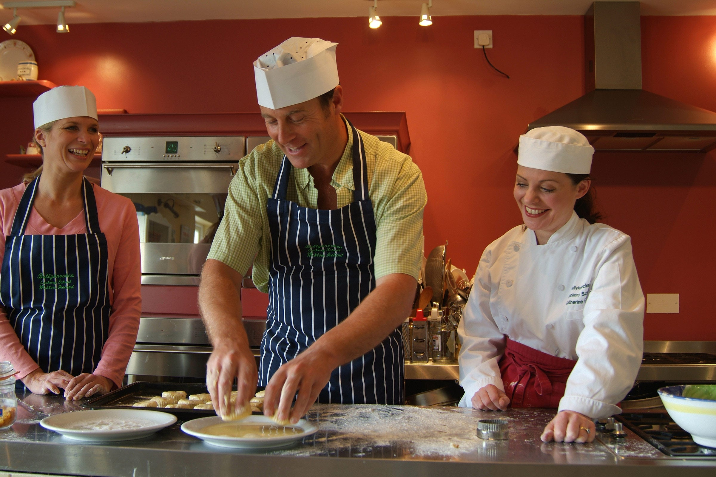A chef showing two students how to cook in a red kitchen in Ballyknocken, County Wicklow