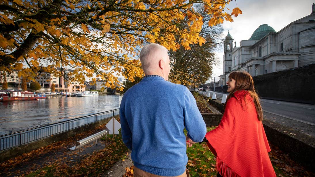 A couple holding hands walking along a tree-lined street in Athlone, County Westmeath
