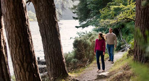 Couple walking on a trail beside a lake in Glendalough, Wicklow
