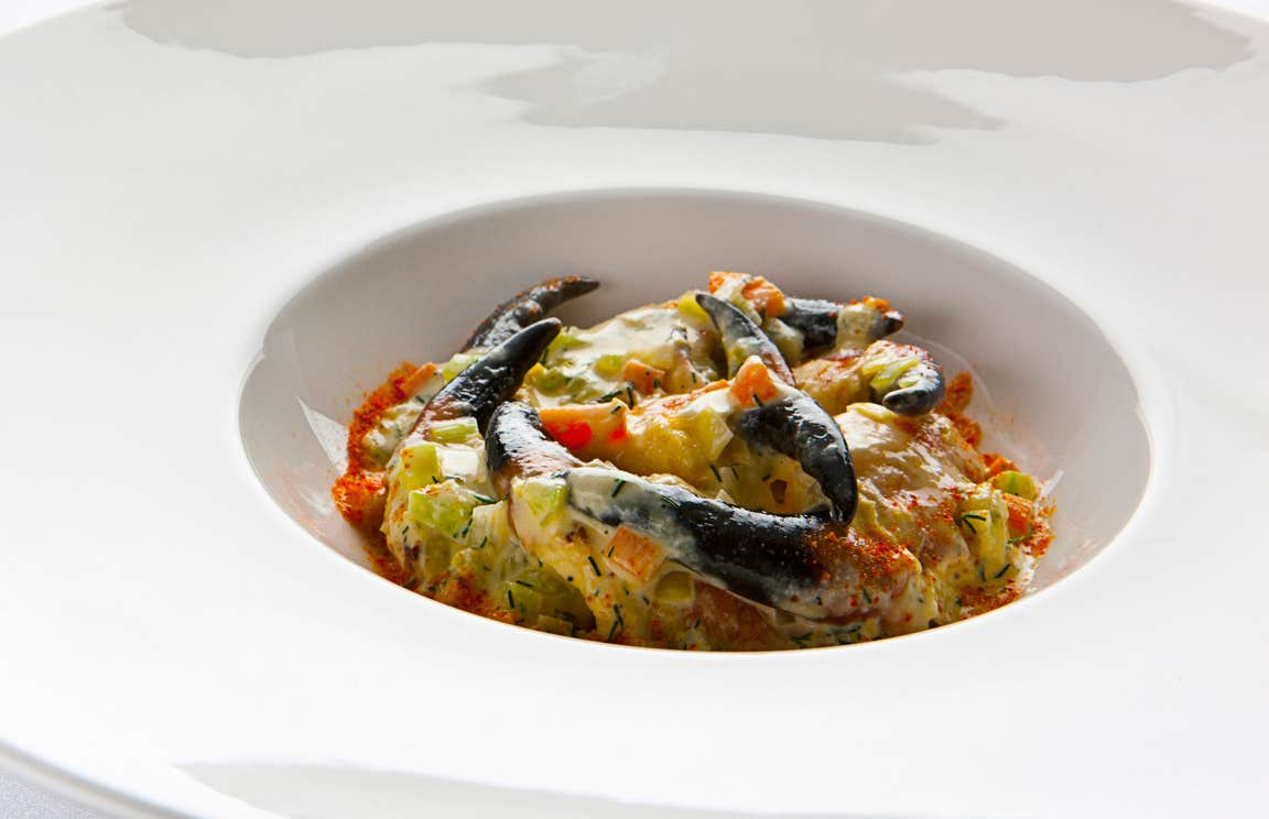 A dish of crabs claws served in a white plate