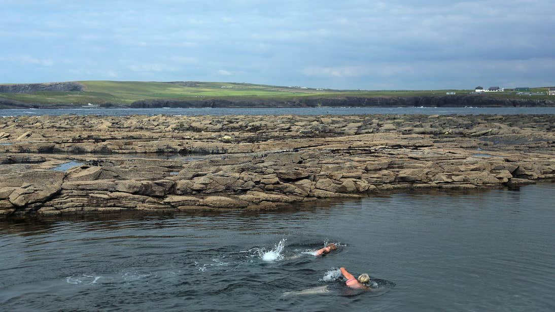 Two people swimming in Kilkee Pollock Holes in County Clare