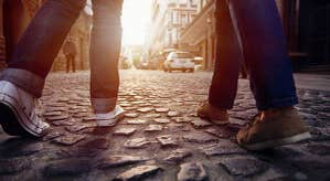 Two people walking along a cobbled street