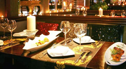 A table set for four in an Indian restaurant with a lit candle on the table and starter dishes to the side