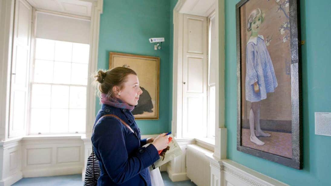 Woman admiring a painting of a young girl at The Hunt Museum in Limerick