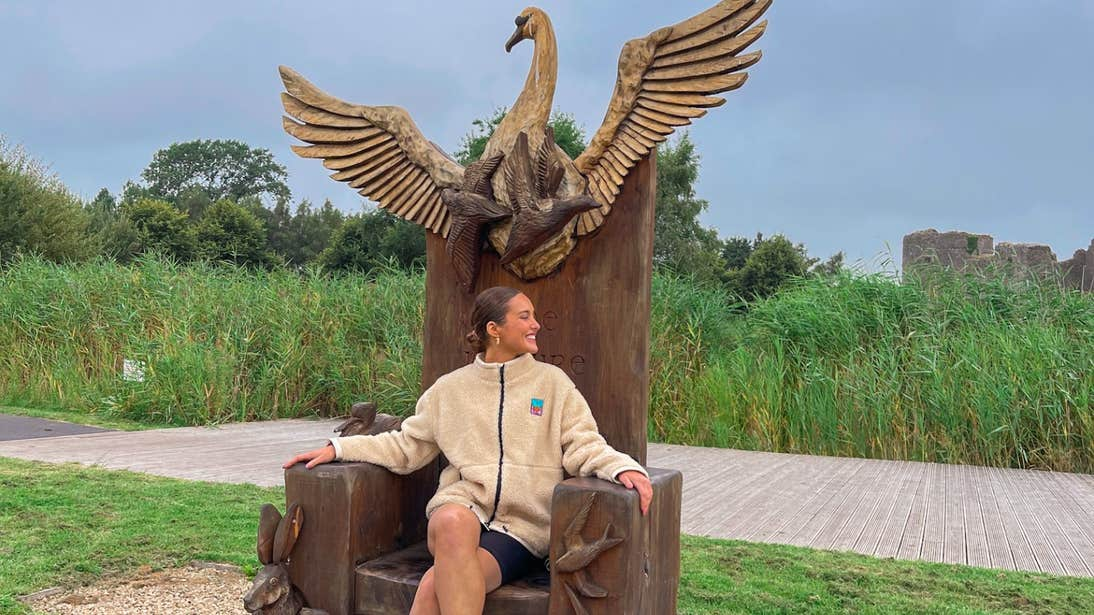 Roz Purcell sitting on a wooden chair carved with animal sculptures on the grounds of Roscommon Castle, Roscommon