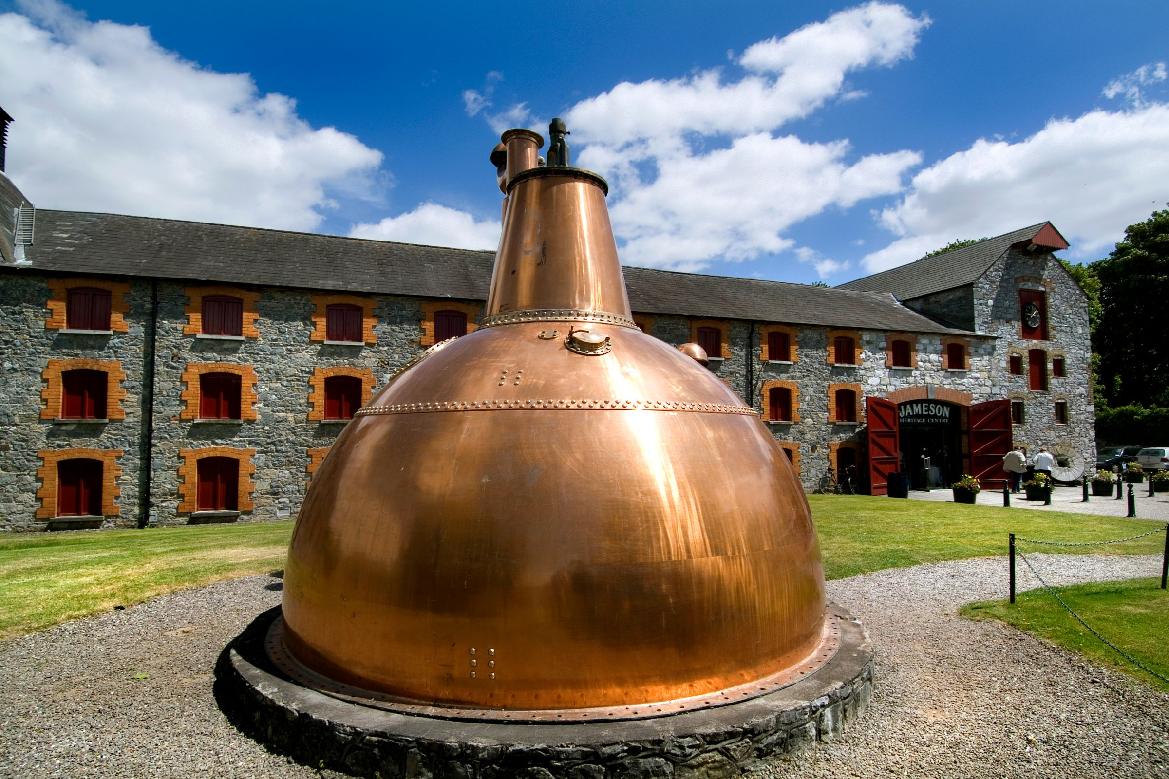 A large copper still outside a stone building.