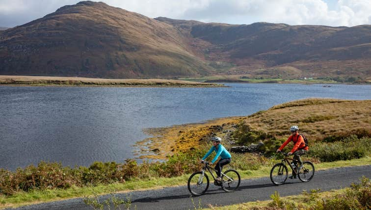 Two people cycling along the Great Western Greenway with sea and mountain views