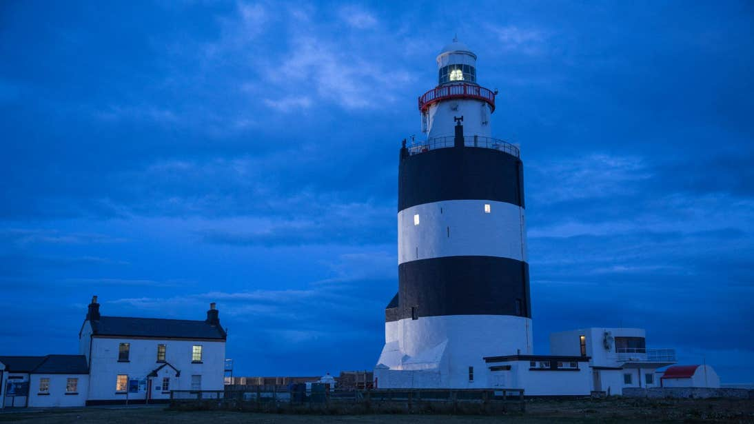 Lighthouse in the evening time beside a house on Hook Head Wexford