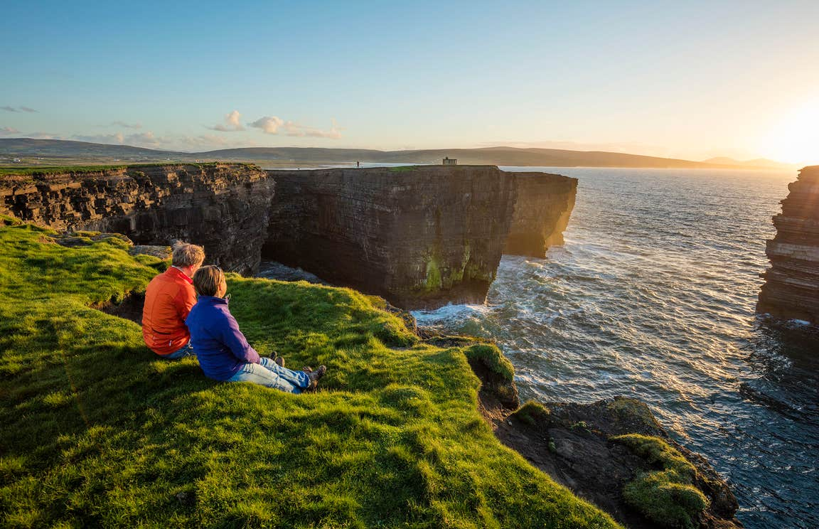 A couple watching the sunset at Downpatrick Head, Co. Mayo