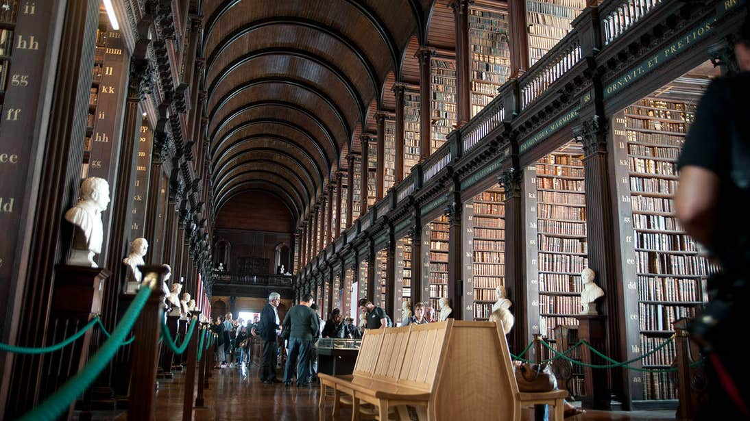 People in a library in Trinity College surrounded by books.
