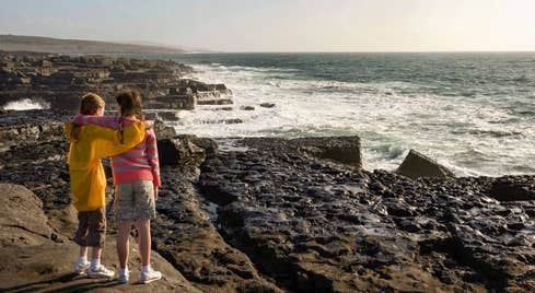 Two young girls looking out at the ocean in The Burren, Co Clare