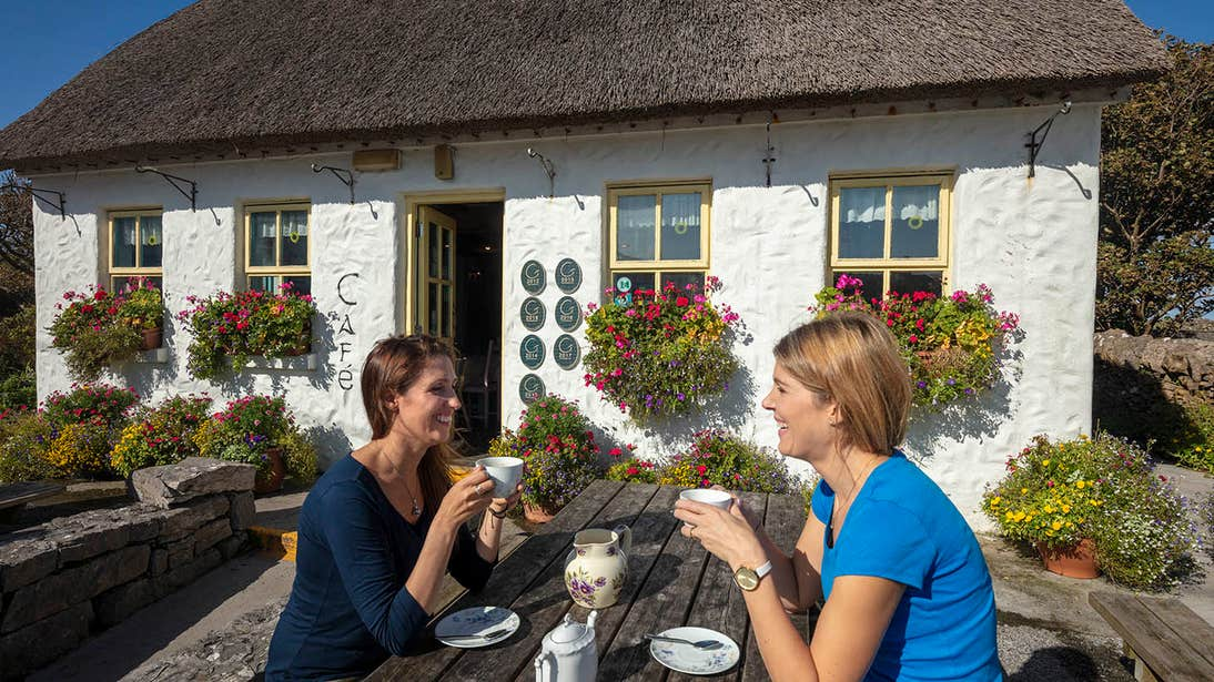 Two people enjoying a cup of tea outside Teach Nan Phaidi, Inishmore, Aran Islands, Galway