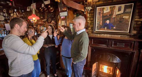 Four people tasting and toasting each other with whiskey by a pub fireside