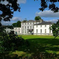 A blue sky and green parklands at Strokestown Park House and Garden