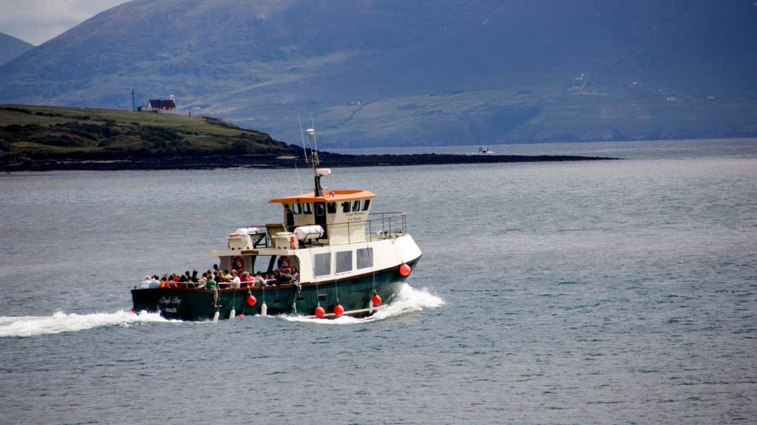 A boat on the water with a backdrop of vast mountains in Dingle, Kerry