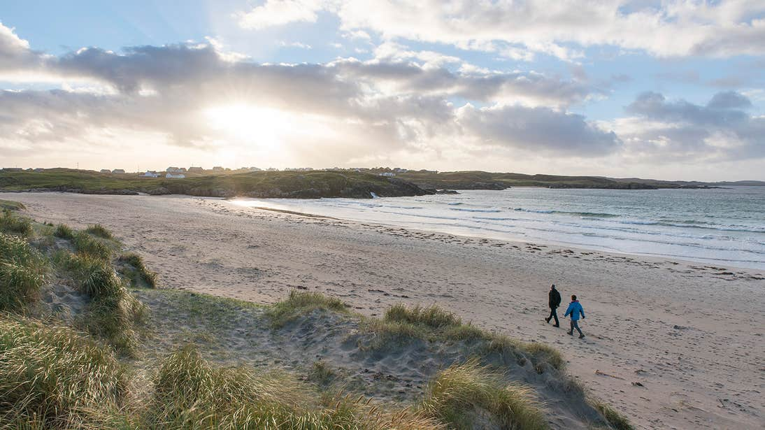 Two people walking down the empty Carrickfinn Beach, Gweedore, Donegal