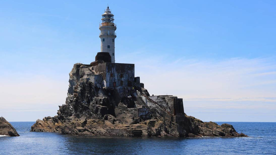 Fastnet Lighthouse on a clear day with blue skies and calm water all around