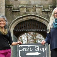 Two ladies standing outside a castle like gate lodge beside a sign that says crafts with an arrow pointing to the right