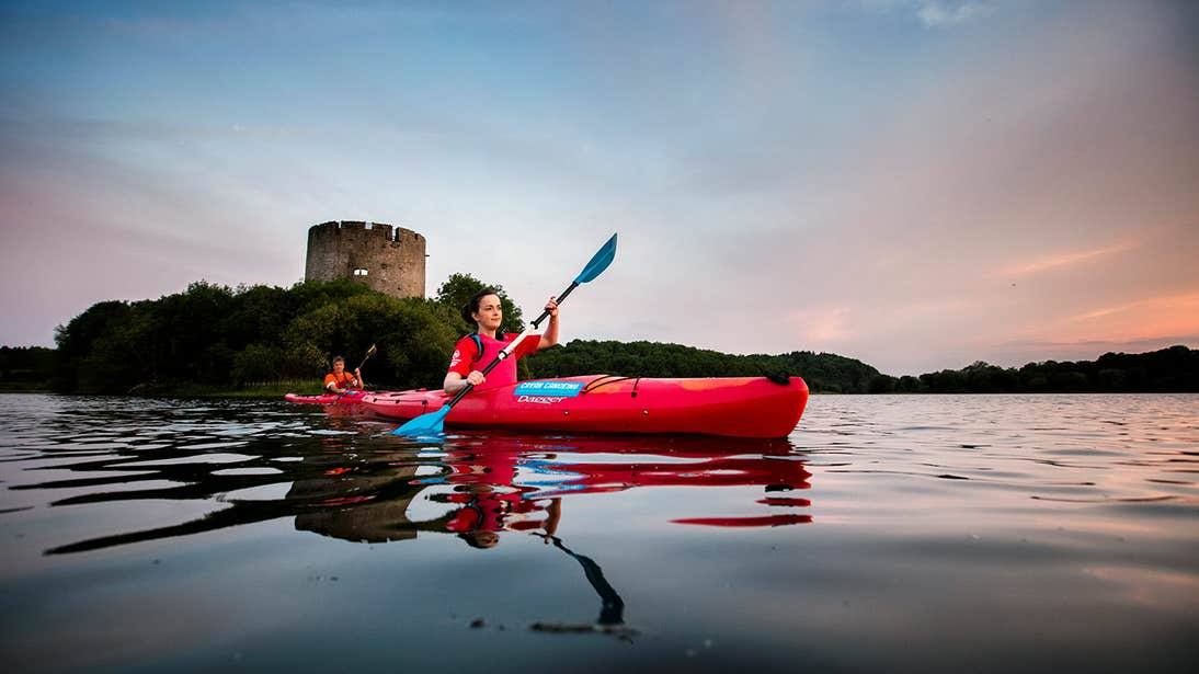Two people kayaking on Lough Oughter in Cavan in front of a castle