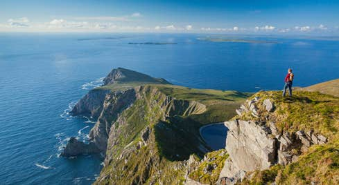 Person standing on a clifftop looking at Croaghaun, Achill Island, Co Mayo