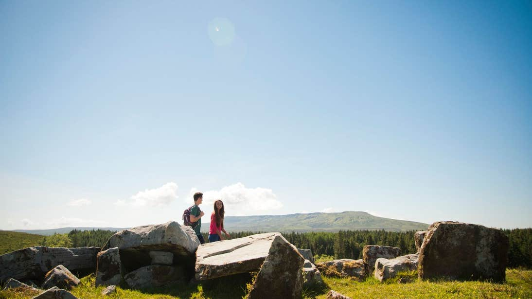 Two people walking by rocks and stone structures in Cavan Burren Park