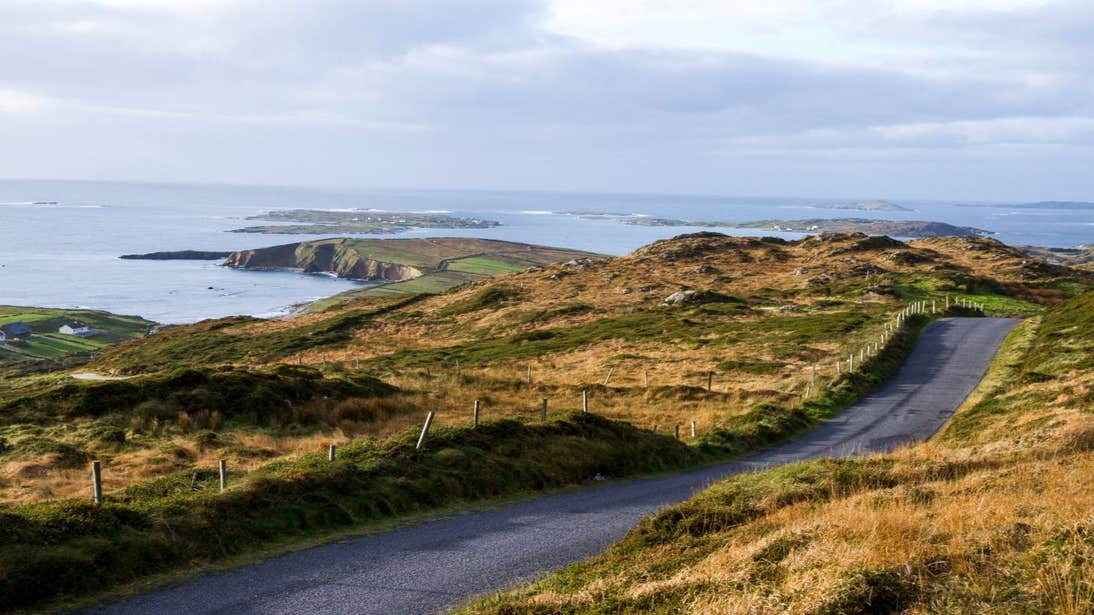 A country lane surrounded by green fields near the coast on Sky Road, Clifden, Galway