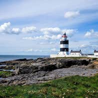 Hook Head Lighthouse beside the sea in Wexford surrounded by rocks and grass.