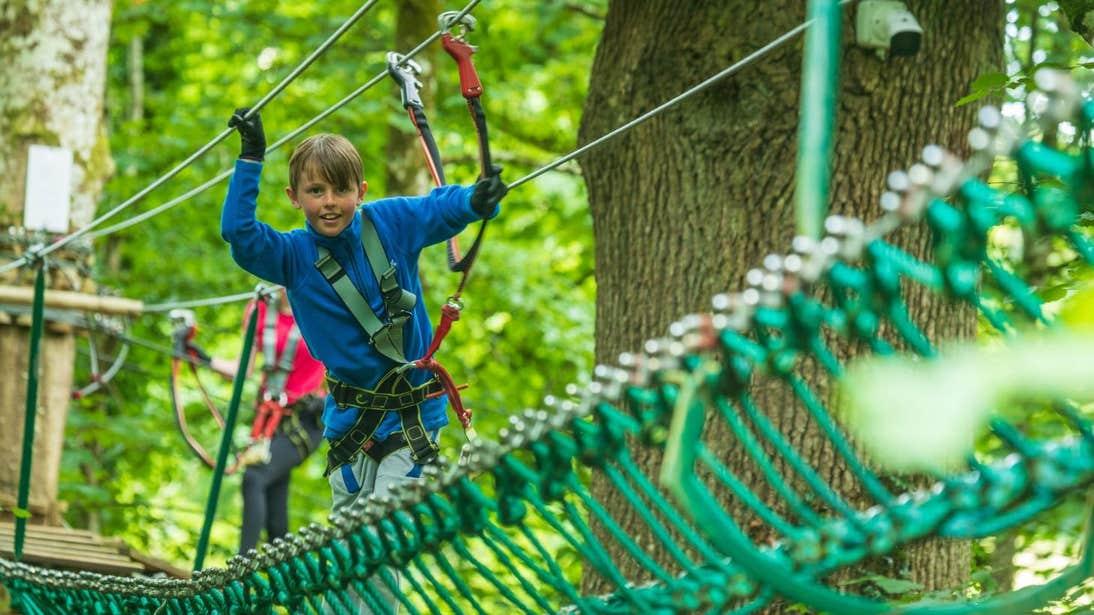 Boy walking across a rope bridge wearing a harness at Zipit Lough Key Ltd, Roscommon