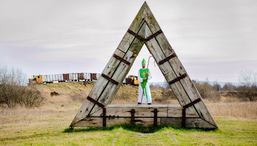 A man dressed in costume standing in the middle of a large wooden triangle in Lough Boora Parklands, County Offaly.