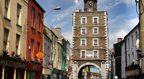 Youghal Clock Gate Tower, shop fronts and cars on a busy street