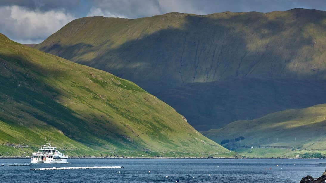 A boat sailing across the water at Killary Harbour with mountains looming in the background