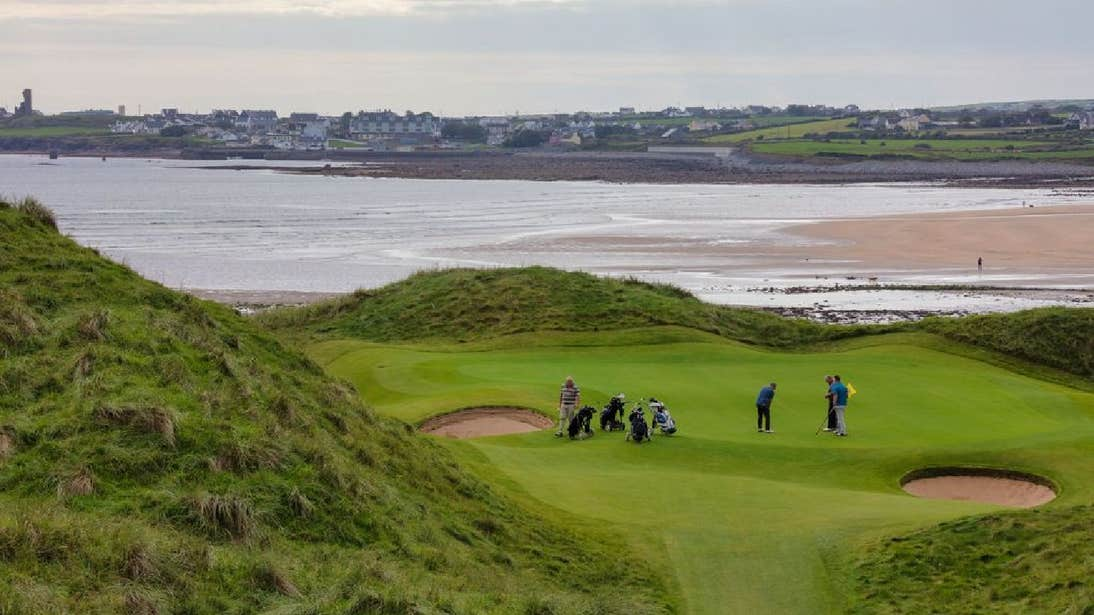 Group of golfers playing golf with coastal views Lahinch Golf Club County Clare