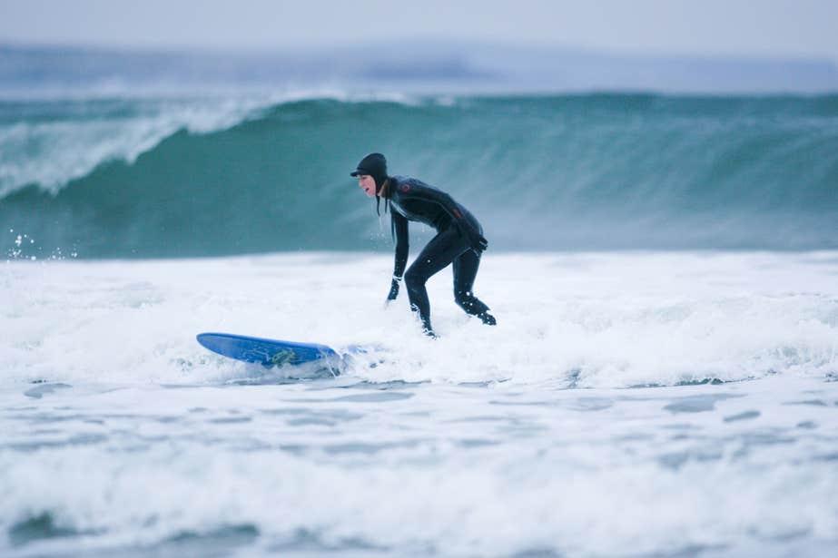 Person surfing on a blue board wearing a full wetsuit in Strandhill, Sligo