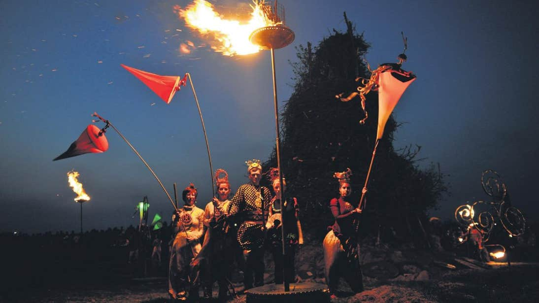 Five people wearing costumes and celebrating the Festival of Fires at Uisneach in Westmeath.