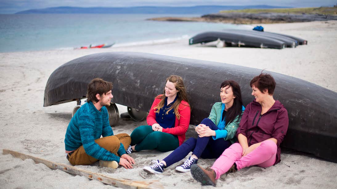 Four people sitting beside a boat on Inisheer Island, Aran islands, Galway