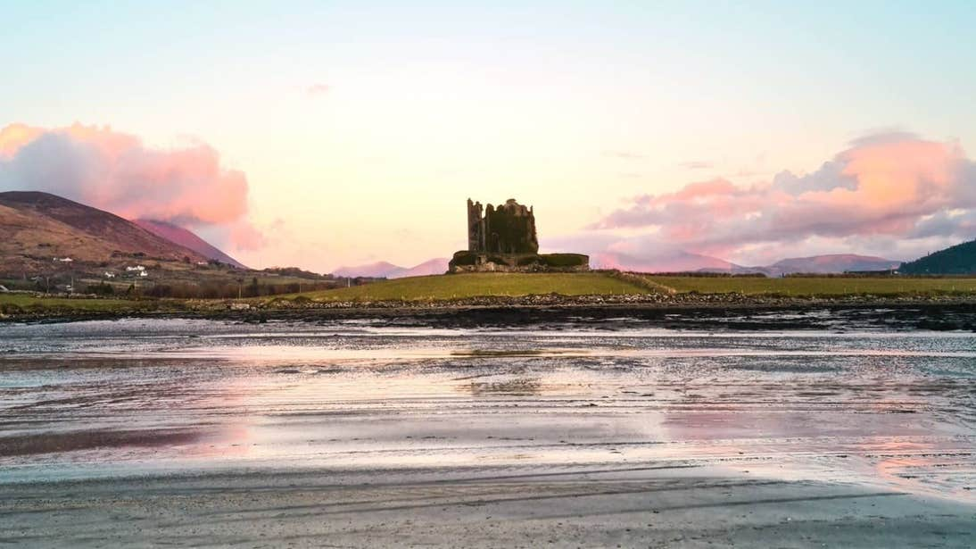A castle beside a river against a backdrop of pastel pink skies in Cahersiveen, Kerry