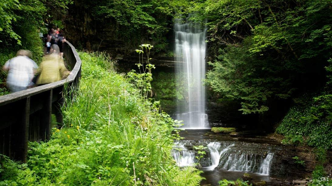 People walking beside Glencar Waterfall, Glencar, County Leitrim