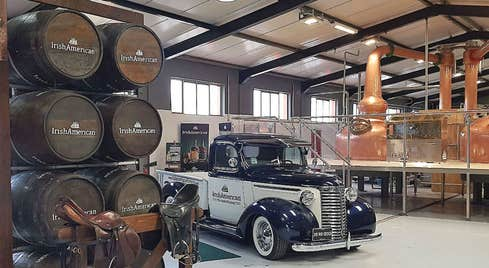 Vintage American car set against the backdrop of the copper distilling pots and stacked whiskey barrels