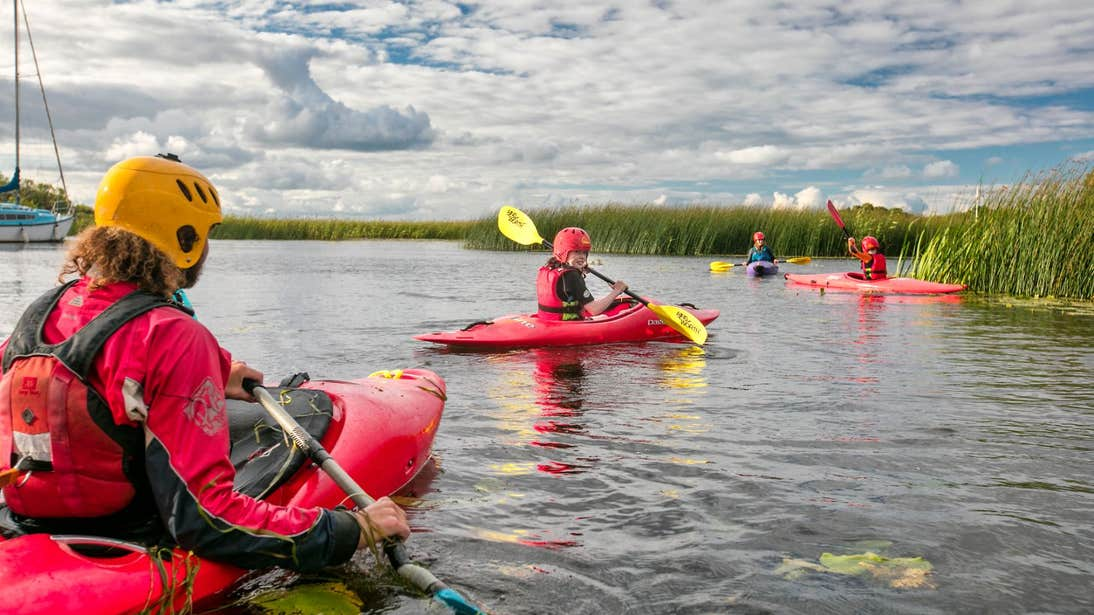 Kayakers in red kayaks paddling near reeds on a Lough Derg County Tipperary