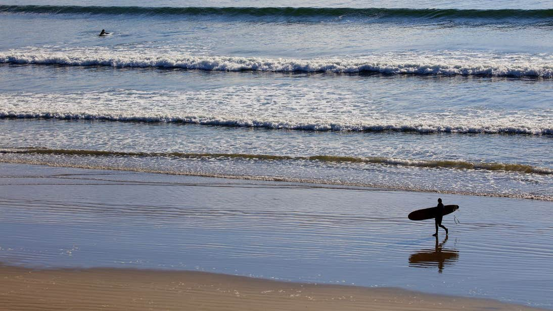 A surfer walks along the beach in Inch Stand, Dingle, Kerry