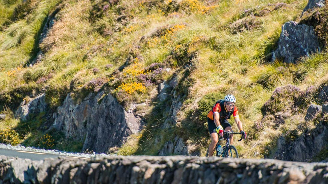 A person cycling past a stone wall on the Ring of Kerry, County Kerry
