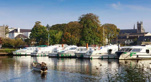 Boats in a marina with a backdrop of trees and a church in Carrick-on-Shannon, County Leitrim