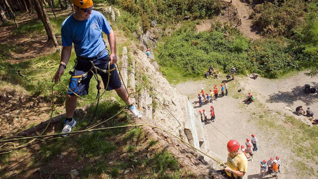 People abseiling down a vertical cliff in Carlingford in Louth