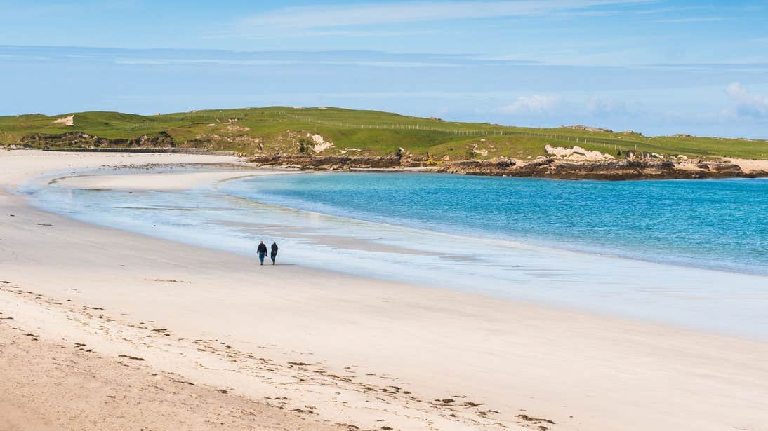 Two people walking along the golden strand of Dog's Bay Beach in County Galway