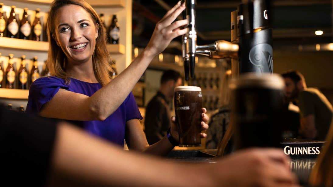 A woman smiling and pulling a pint at the Guinness Storehouse, Dublin